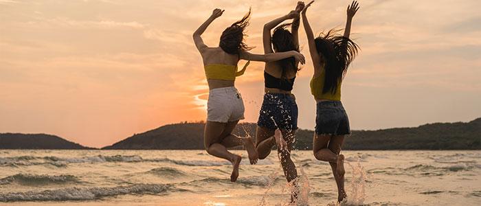 Chicas saltando felices en una playa de Australia