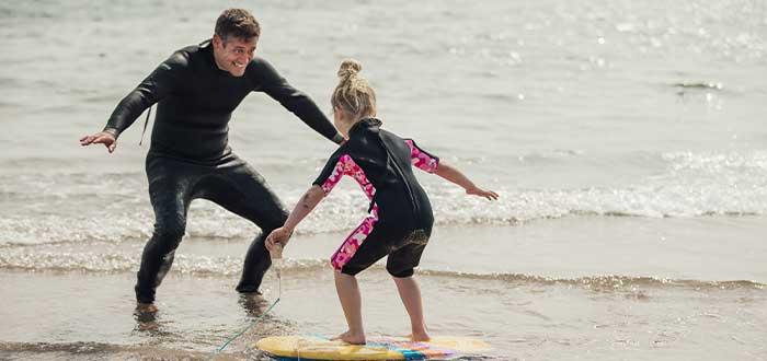 Hombre enseña a surfear a niña