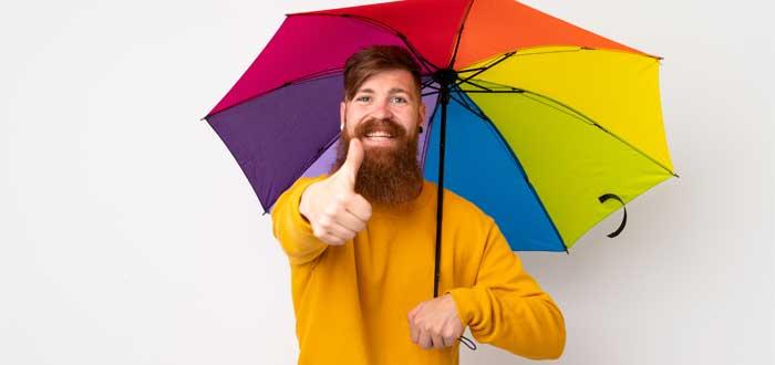 Hombre sosteniendo un paraguas multicolor.